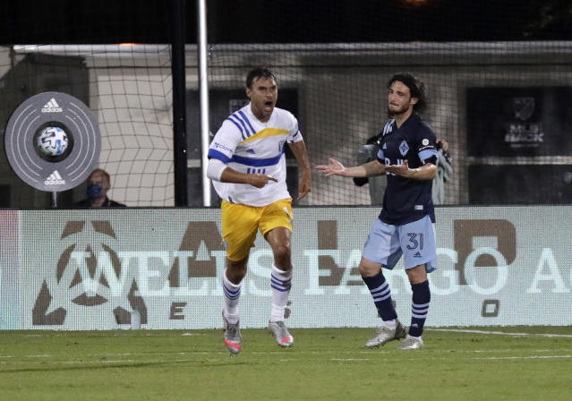 San Jose Earthquakes forward Chris Wondolowski, left, celebrates after scoring a goal as Vancouver Whitecaps midfielder Russell Teibert (31) reacts during the second half of an MLS soccer match Wednesday, July 15, 2020, in Kissimmee, Fla. (AP Photo/John Raoux)