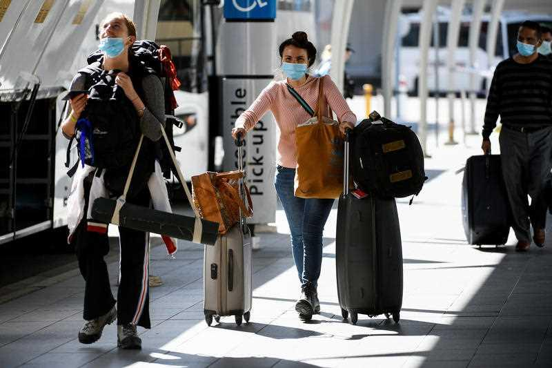 Australian residents returning from India are ushered towards waiting busses for the beginning of their 14-day imposed quarantine after arriving at Sydney International Airport.