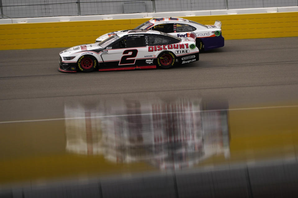 Brad Keselowski (2) and Denny Hamlin drive during a NASCAR Cup Series auto race Sunday, March 7, 2021, in Las Vegas. (AP Photo/John Locher)