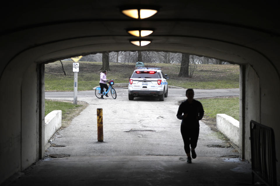 A Chicago police officer notifies a cyclist that the trails along Lake Michigan are closed in an effort to limit the spread of COVID-19 infections, Thursday, March 26, 2020, in Chicago. The new coronavirus causes mild or moderate symptoms for most people, but for some, especially older adults and people with existing health problems, it can cause more severe illness or death. (AP Photo/Charles Rex Arbogast)