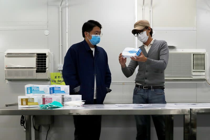 Mask Factory founder Mr. Tang talks to a colleague at his factory, following the outbreak of the new coronavirus, in Hong Kong
