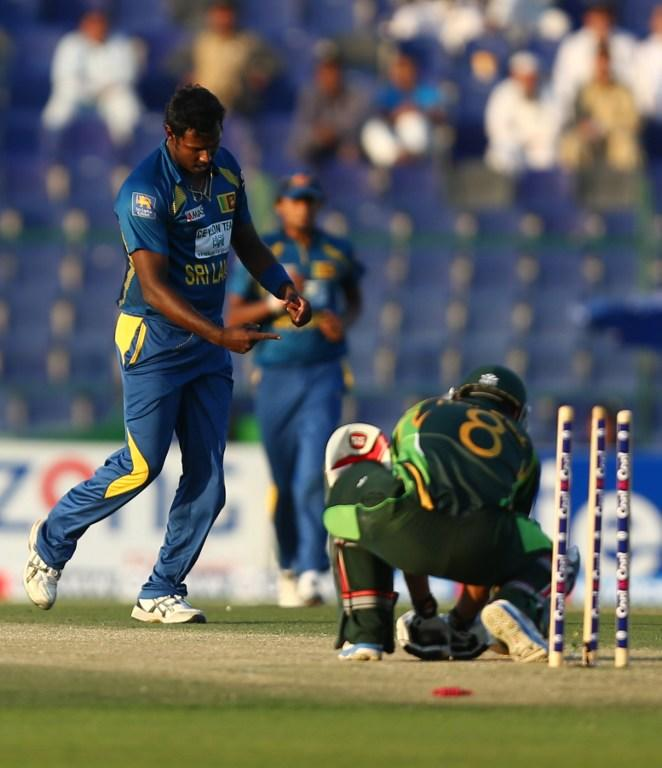 Bowler Angelo Mathews (L) of Sri Lanka gestures after dismissing batsman Mohammad Hafeez (R) of Pakistan during the fifth and final One Day International cricket match between Pakistan and Sri Lanka in Abu Dhabi on December 27, 2013. AFP PHOTO/MARWAN NAAMANI