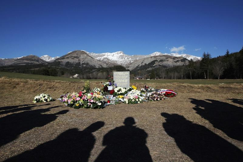 People stand near a stela commemorating the victims of the March 24 Germanwings Airbus A320 crash in the village of Le Vernet, southeastern France, on April 6, 2015 after a ceremony with victims' relatives