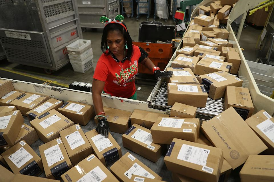 U.S. Postal service mail handler Barbara Lynn sorts boxes at the U.S. Postal service's Royal Palm Processing and Distribution Center on December 4, 2017, in Opa Locka, Florida. (Photo by Joe Raedle/Getty Images)