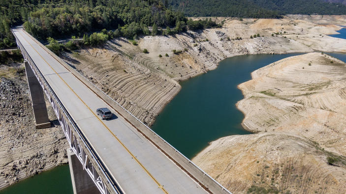 A car crosses Enterprise Bridge over Lake Oroville's dry banks Sunday, May 23, 2021, in Oroville, Calif. At the time of this photo, the reservoir was at 39 percent of capacity and 46 percent of its historical average. California officials say the drought gripping the U.S. West is so severe it could cause one of the state's most important reservoirs to reach historic lows by late August, closing most boat ramps and shutting down a hydroelectric power plant during the peak demand of the hottest part of the summer. (AP Photo/Noah Berger)