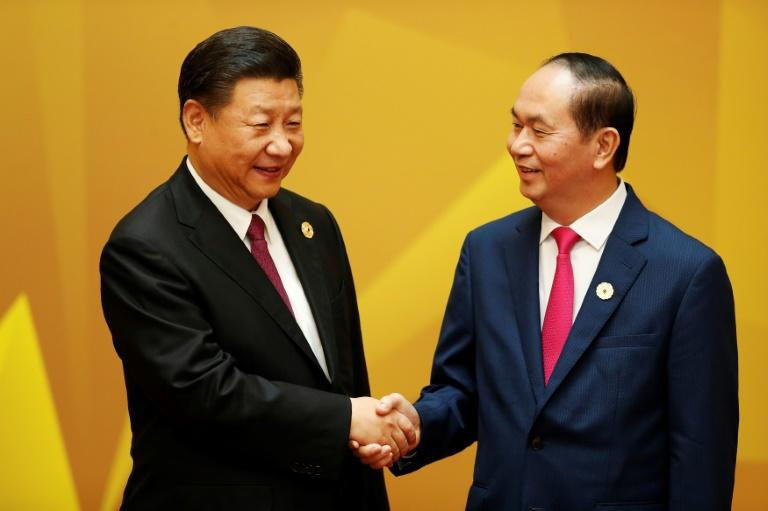 China's President Xi Jinping (L) shakes hands with Vietnam's President Tran Dai Quang upon arrival for the APEC Economic Leaders' Meeting