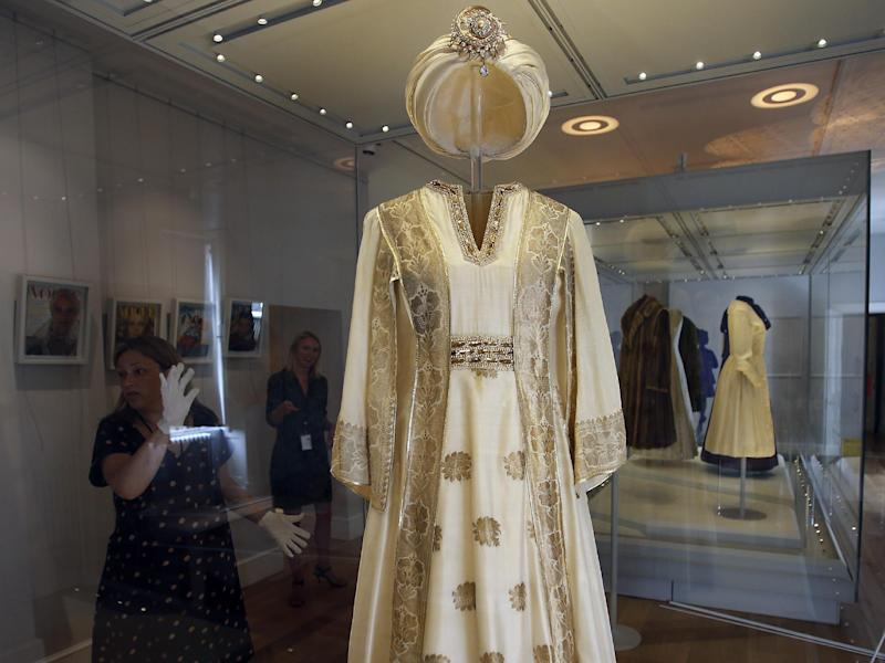 In this photo taken Monday, July 1, 2013, an employee cleans the glass cabinet showing a turban dress worn by Princess Margaret, at the Fashion Rules exhibition at Kensington Palace in London. Opening on 4 July, a new glamorous exhibit at Kensington Palace showcases how the styles of three royal ladies; Queen Elizabeth II, her sometimes risque sister Margaret, and the glamorous Princess Diana, each reflected and influenced the trends of their fashion heyday. (AP Photo/Frank Augstein)