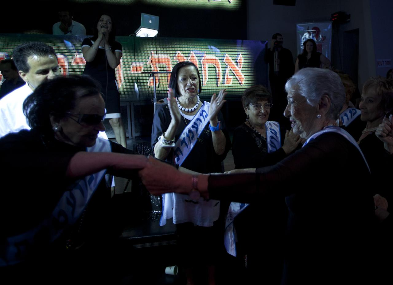 "Holocaust survivors dance as they participate in a beauty pageant, in the northern Israeli city of Haifa, Thursday, June 28, 2012. Fourteen women who lived through the horrors of World War II paraded on stage Thursday night in an unusual pageant, vying for the honor of being Israel's first ""Miss Holocaust Survivor."" (AP Photo/Sebastian Scheiner)"