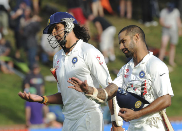 India's Ishant Sharma, left and Shikar Dhawan leave the pitch at the end of play against New Zealand on the first day of the second cricket test in Wellington, New Zealand, Friday, Feb. 14, 2014. (AP Photo/SNPA, Ross Setford) NEW ZEALAND OUT