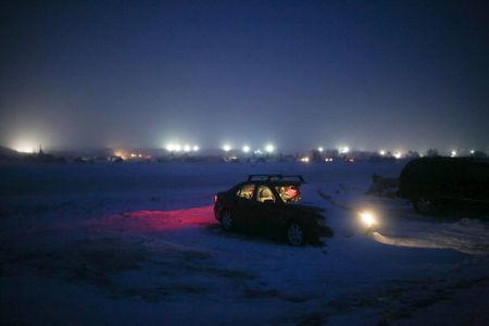 "A woman is seen sitting inside her vehicle during dusk in the Rosebud camp where ""water protectors"" continue to demonstrate against plans to pass the Dakota Access pipeline adjacent to the Standing Rock Indian Reservation, near Cannon Ball, North Dakota, U.S., December 7, 2016.  Picture taken December 7, 2016.   REUTERS/Stephen Yang"