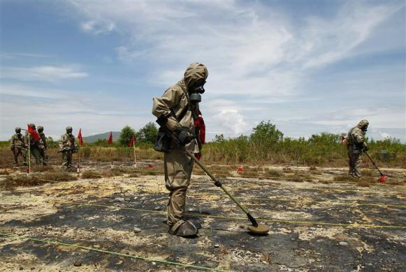 "Soldiers detect Unexploded Ordnance and defoliant Agent Orange during the launch of the ""environmental remediation of dioxin contamination"" project, in Vietnam's central Da Nang City, June 17, 2011. The U.S. is now formally involved in the clean-up of Agent Orange contamination in Vietnam."