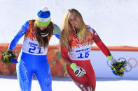 <p>Gold medallists Slovenia's Tina Maze and Switzerland's Lara Gut joke on the podium at the Women's Alpine Skiing Downhill Flower Ceremony at the Rosa Khutor Alpine Center during the Sochi Winter Olympics on February 12, 2014. AFP PHOTO / ALEXANDER KLEIN (Photo credit should read ALEXANDER KLEIN/AFP/Getty Images) </p>
