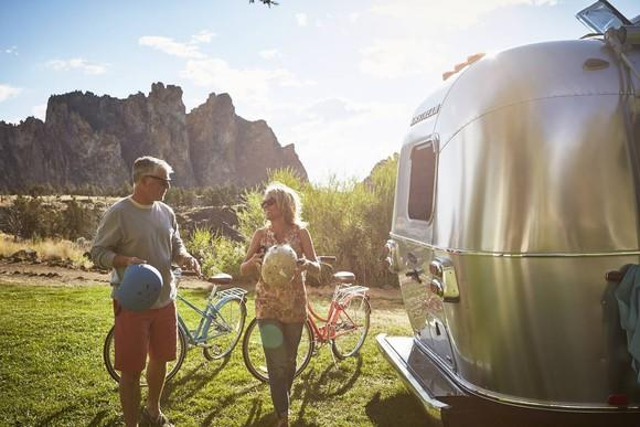 Husband and wife standing with bicycles near an Airstream RV.