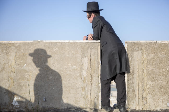 An ultra-Orthodox youth watches the funeral of Shragee Gestetner, a Canadian singer who died during Lag BaOmer celebrations at Mt. Meron in northern Israel, in Jerusalem on Friday, April 30, 2021. A stampede at the religious festival attended by tens of thousands of ultra-Orthodox Jews in northern Israel killed dozens of people and injured about 150 early Friday, medical officials said. It was one of the country's deadliest civilian disasters. (AP Photo/Ariel Schalit)