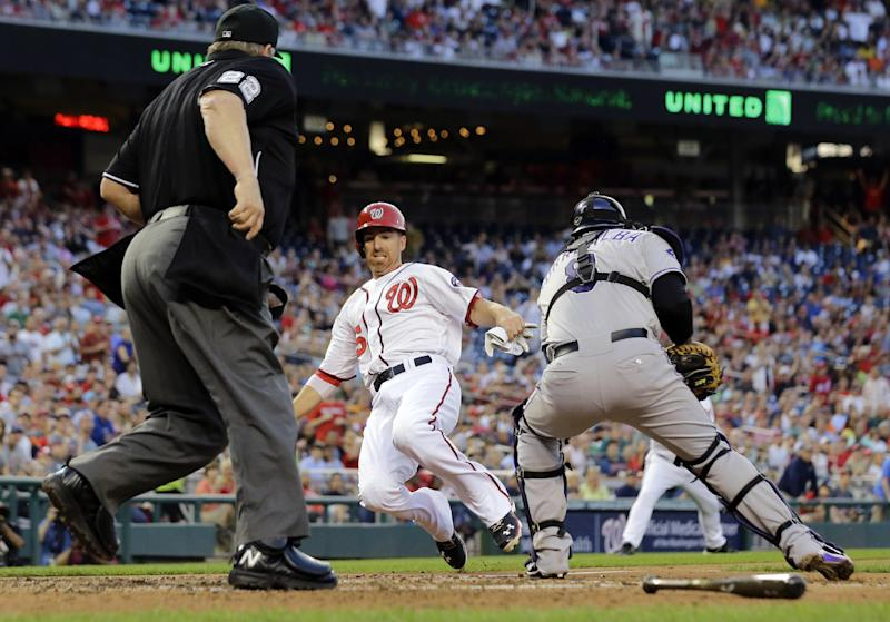 Home plate umpire Joe West, left, watches as Washington Nationals' Adam LaRoche, center, slides safely into home plate as Colorado Rockies catcher Yorvit Torrealba, right, attempts to tag him out during the fourth inning of a baseball game at Nationals Park, Thursday, June 20, 2013, in Washington. (AP Photo/Alex Brandon)