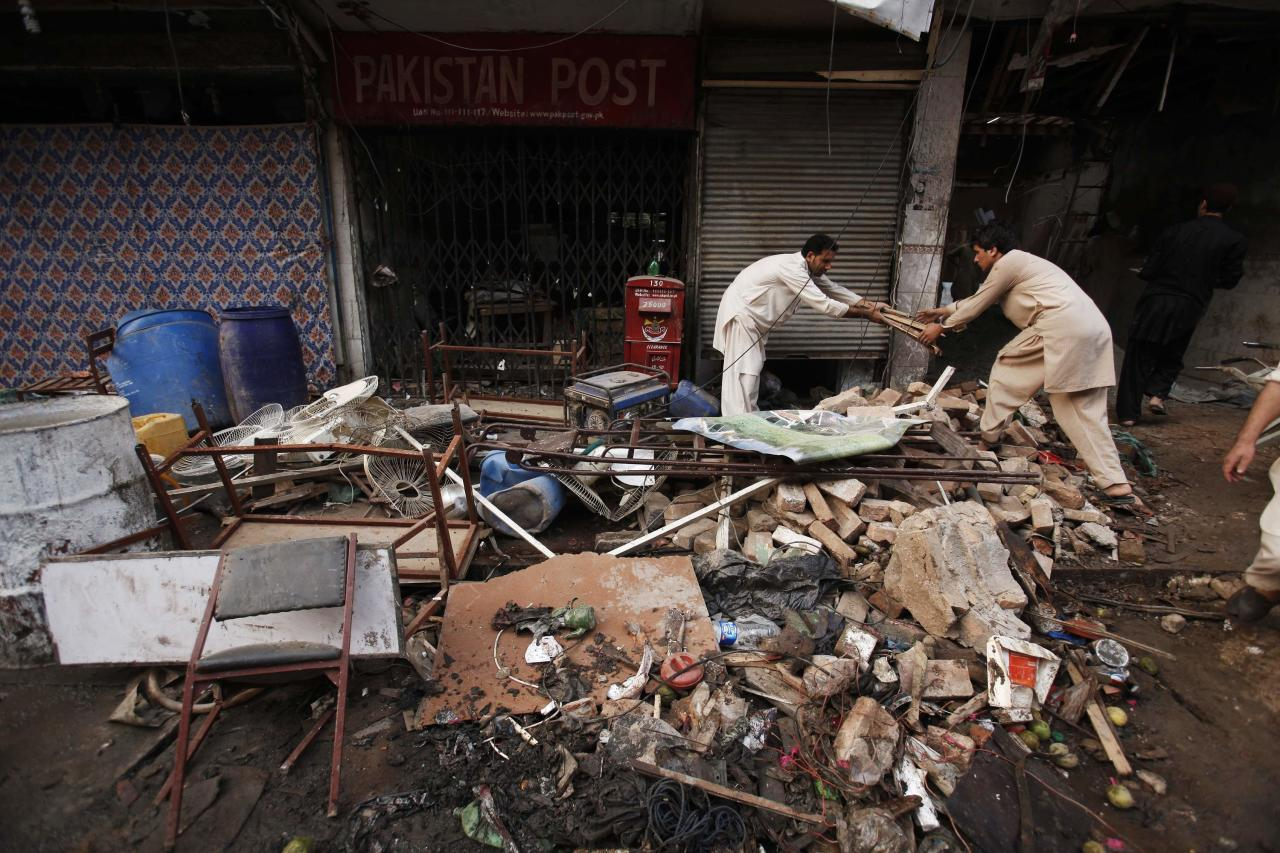 Men collect their belongings from the debris of a damaged building after it was hit by a bomb blast, which happened on Sunday, in Peshawar September 30, 2013. The death toll from a car bomb explosion in an ancient market in Pakistan's northwestern city of Peshawar rose to at least 42 on Monday, after the third attack in the area in a week. The blast ripped through the busy centuries-old market known as Quiswakhani, or the storytellers' bazaar, in Peshawar's old city on Sunday, exactly a week after more than 80 Christians were killed in a twin suicide bomb attack on a nearby church. REUTERS/Fayaz Aziz (PAKISTAN - Tags: POLITICS CIVIL UNREST)