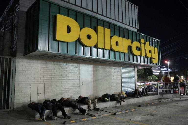 "Salvadoran migrants huddled on the sidewalk in front of a shop called ""Dollarcity"" before a caravan departed"