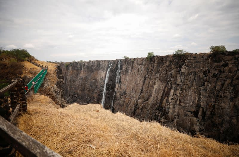 Visitors walk over a bridge as dry cliffs are seen along the parched gorge on the Zambian side of Victoria Falls