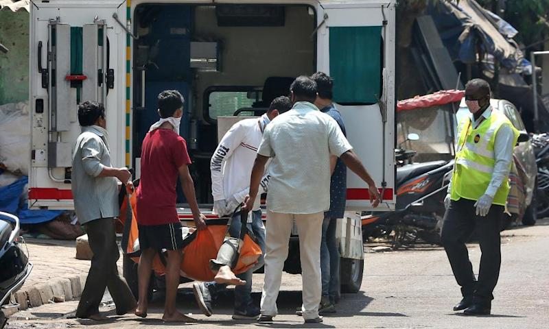 Health workers carry a man with suspected coronavirus into an ambulance in Dharavi.