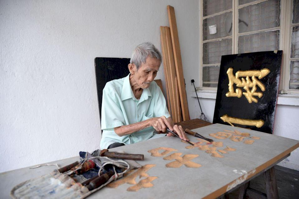 Kok with some of the signboards he carved.