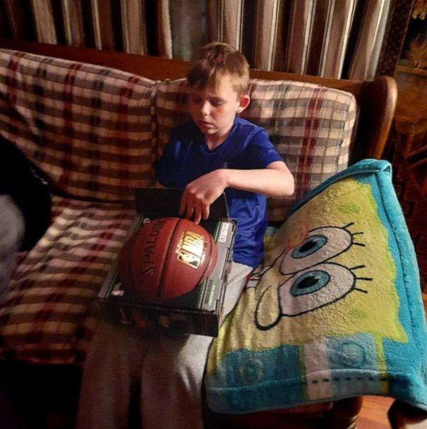 PHOTO: Boy holding basketball gifted by FedEx driver. (Coledo Wheeler via Storyful)