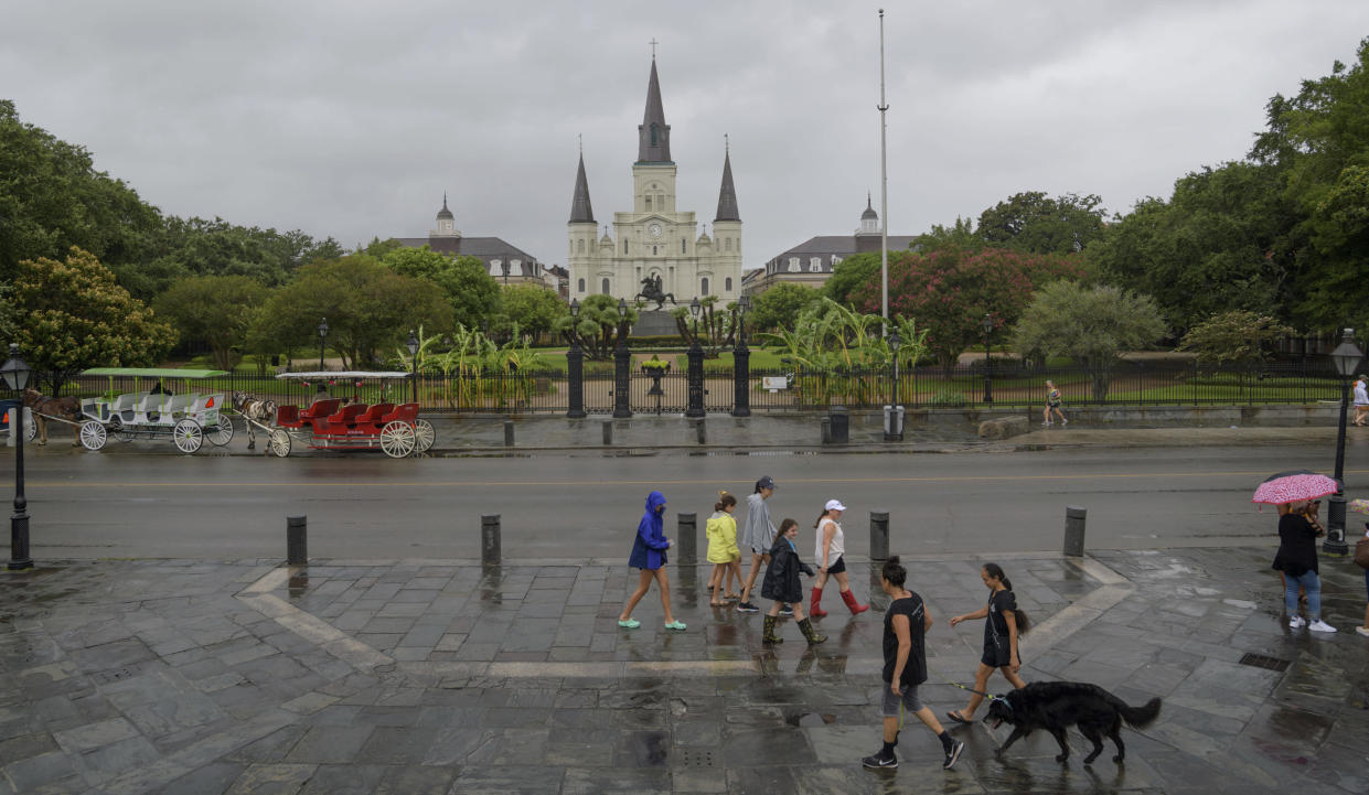 People walk past Jackson Square and St. Louis Cathedral in the French Quarter before landfall of Tropical Storm Barry from the Gulf of Mexico in New Orleans, La., Friday, July 12, 2019. (Photo: Matthew Hinton/AP)