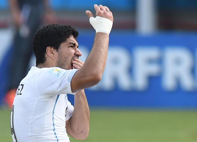 Uruguay forward Luis Suarez puts his hand to his mouth after clashing with Italy's defender Giorgio Chiellini during a Group D football match between Italy and Uruguay at the Dunas Arena in Natal during the 2014 FIFA World Cup on June 24, 2014 (AFP Photo/Javier Soriano)