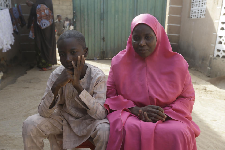 Usman Mohammad Rabiu, a 13 year old student of Government Science Secondary School Kankara, sits with his mother Asmau Hassan at their family house in Ketare, Nigeria, and speaks to the Associated Press, Saturday Dec. 19, 2020. Nigeria's freed schoolboys have reunited with their joyful parents after being held captive for nearly a week by gunmen allied with jihadist rebels in the country's northwest. Relieved parents hugged their sons tightly on Saturday in Kankara, where more than 340 boys were abducted from the Government Science Secondary school on the night of Dec. 11. (AP Photo/Sunday Alamba)