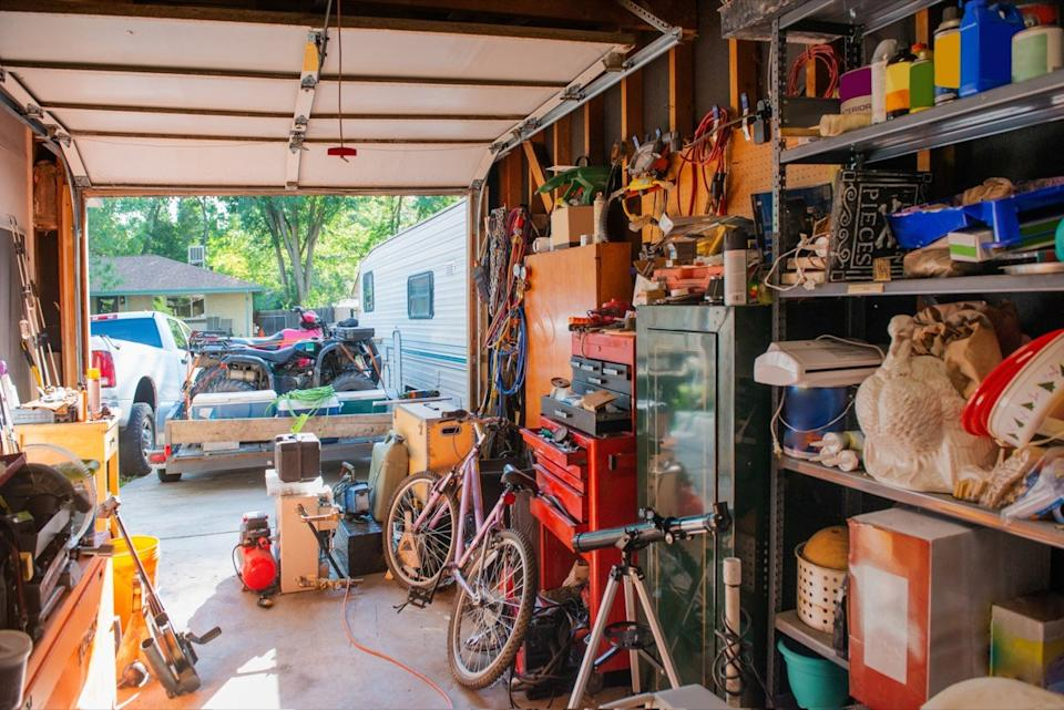 This photograph is of a garage lined with shelves full of things stored at home including, tools, cleaning supplies, holiday decorations and sporting equipment. The garage door is open.