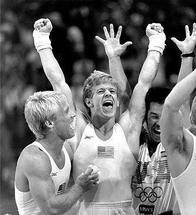 "Bart Conner, left, and Peter Vidmar, center, celebrate following the U.S. men's gymnastic team's gold medal triumph on July 31, 1984. <span class=""copyright"">(Rusty Kennedy / Associated Press)</span>"