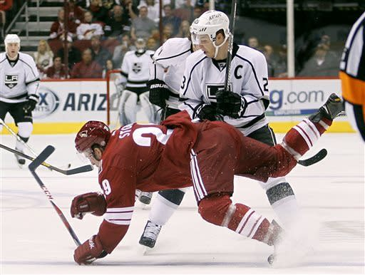 Los Angeles Kings right winger Dustin Brownm, top, checks Phoenix Coyotes defenseman Michael Stone, bottom, to the ice in the first period of an NHL hockey game Tuesday, April 2, 2013, in Glendale, Ariz. (AP Photo/Paul Connors)