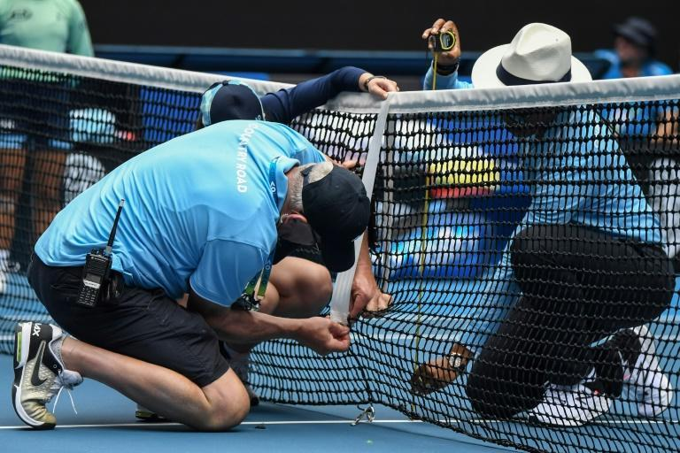 Officials repair the net broken by a Naomi Osaka serve on Rod Laver Arena (AFP Photo/William WEST)
