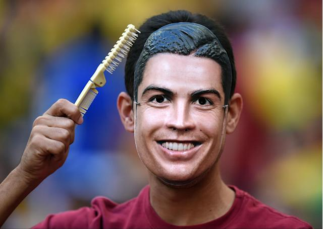 A Portugal supporter wears a Ronaldo mask before the group G World Cup soccer match between Portugal and Ghana at the Estadio Nacional in Brasilia, Brazil, Thursday, June 26, 2014. (AP Photo/Paulo Duarte)