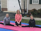 Jamie Burton, of Glen Allen, Va., and her two daughters, Josie, 12, left, and Cayden, 9, right, outside their home Thursday, March 26, 2020 on gymnastics mats. The Burtons have had more time together because the girls' nightly gymnastics practices have been canceled because of the coronavirus outbreak. (AP Photo/Denise Lavoie)