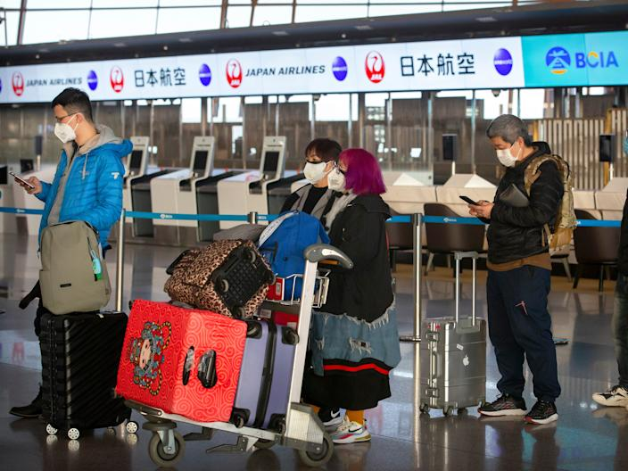 Travelers wearing face masks line up near the Japan Airlines check-in counters at Beijing Capital International Airport in Beijing, Thursday, Jan. 30, 2020. China counted 170 deaths from a new virus Thursday and more countries reported infections, including some spread locally, as foreign evacuees from China's worst-hit region returned home to medical observation and even isolation. (AP Photo/Mark Schiefelbein)