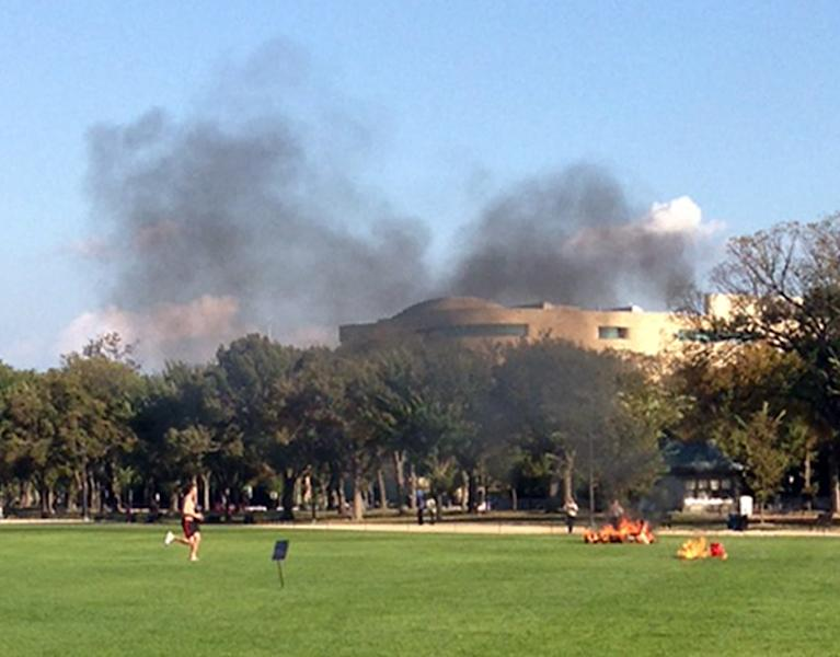 In this photo provided by Katy Scheflen, people run to a man who set himself on fire on the National Mall in Washington, Friday, Oct. 4, 2013. The reason for the self-immolation was not immediately clear and the man's identity was not disclosed. (AP Photo/Katy Scheflen)