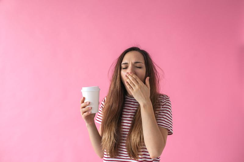 Cute girl with a glass of coffee in hand is yawning. She can't wake up.