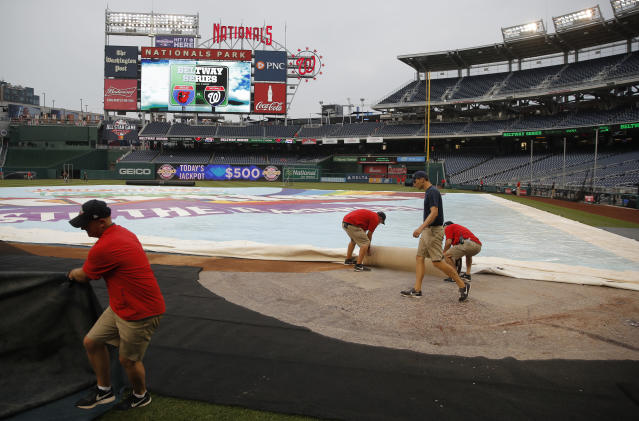 Members of the grounds crew adjust the tarp on the field before baseball game between the Washington Nationals and the Baltimore Orioles at Nationals Park, Wednesday, June 20, 2018, in Washington. (AP Photo/Carolyn Kaster)