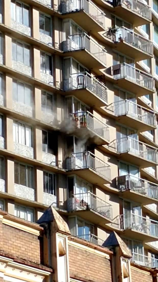 Smoke billows from the 11th floor of a 23-storey building in Vancouver's West End on Saturday, May 29, 2021. Vancouver Fire and Rescue confirmed the next day that the occupant of the suite later died of his injuries.  (Daniella Moore - image credit)