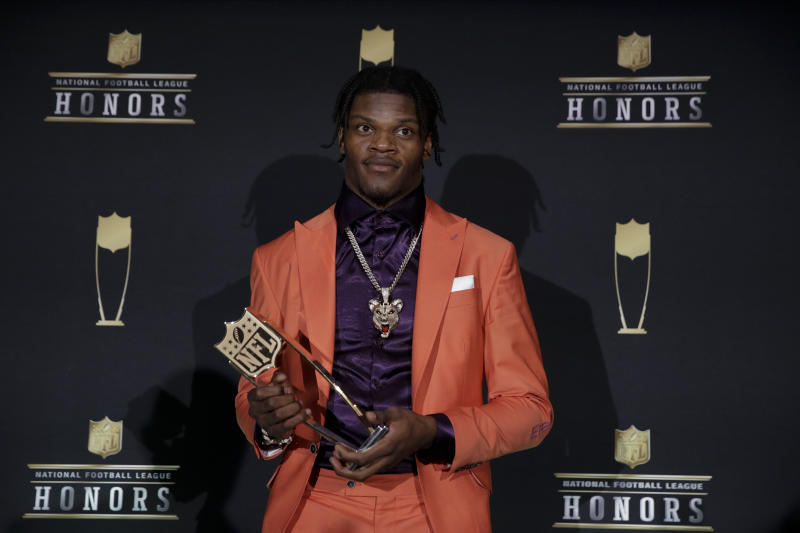 Lamar Jackson holds the AP Most Valuable Player award in front of an NFL Honors backdrop.