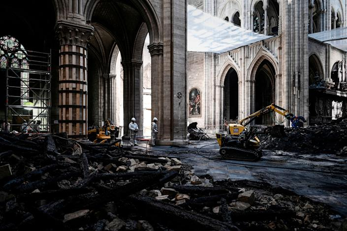 Workers stand near damages and rubble during preliminary work inside the Notre Dame de Paris Cathedral, May 15, 2019 in Paris. (Photo: Philippe Lopez/Pool via AP)