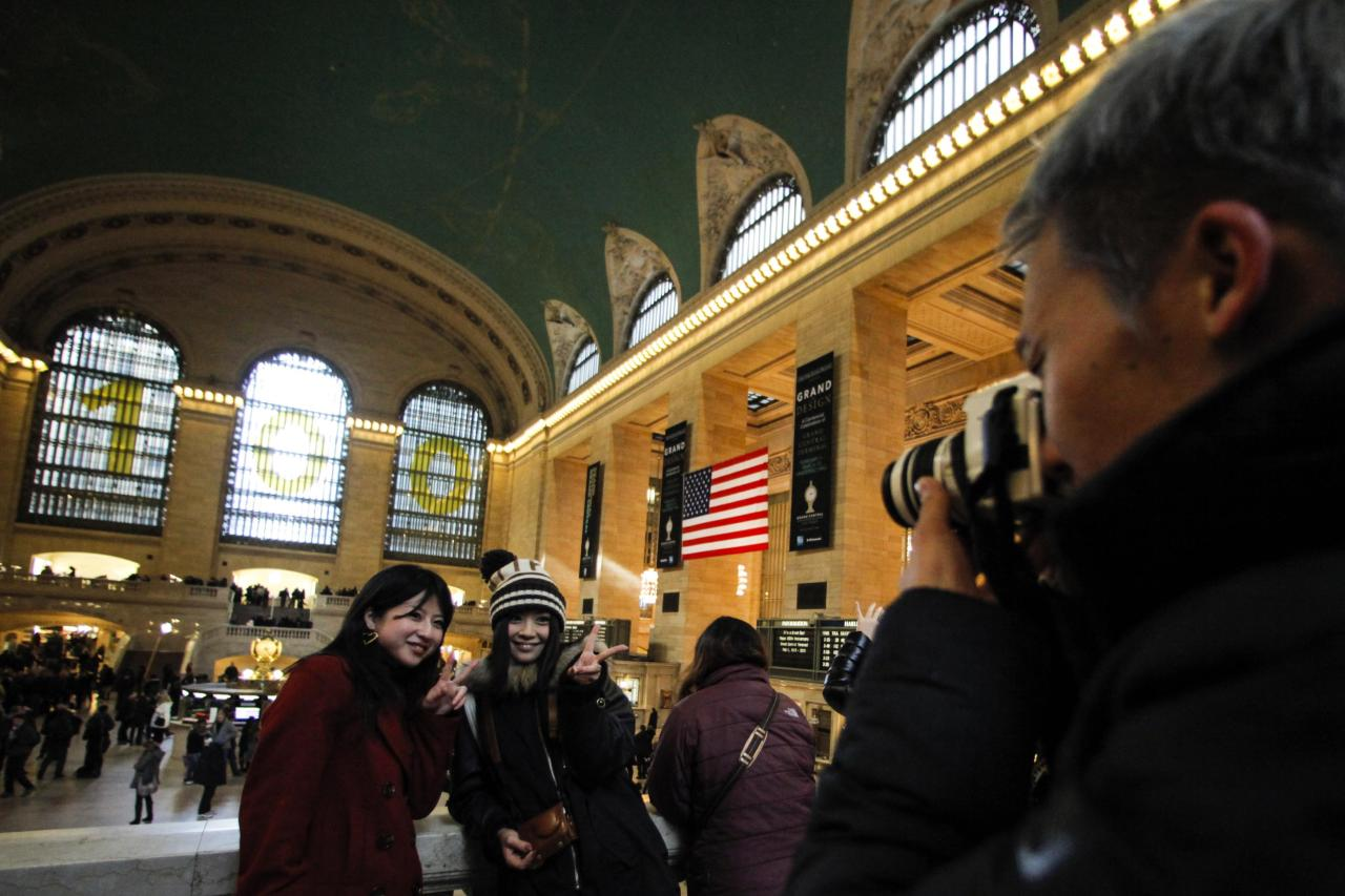 Tourists pose for a picture inside Grand Central Station in New York, February 2, 2013. Grand Central Terminal, the doyenne of American train stations, is celebrating its 100th birthday. Opened on February 2, 1913, the iconic New York landmark with its Beaux-Arts facade is an architectural gem, and still one of America's greatest transportation hubs. REUTERS/Eduardo Munoz (UNITED STATES - Tags: ANNIVERSARY TRANSPORT TRAVEL)