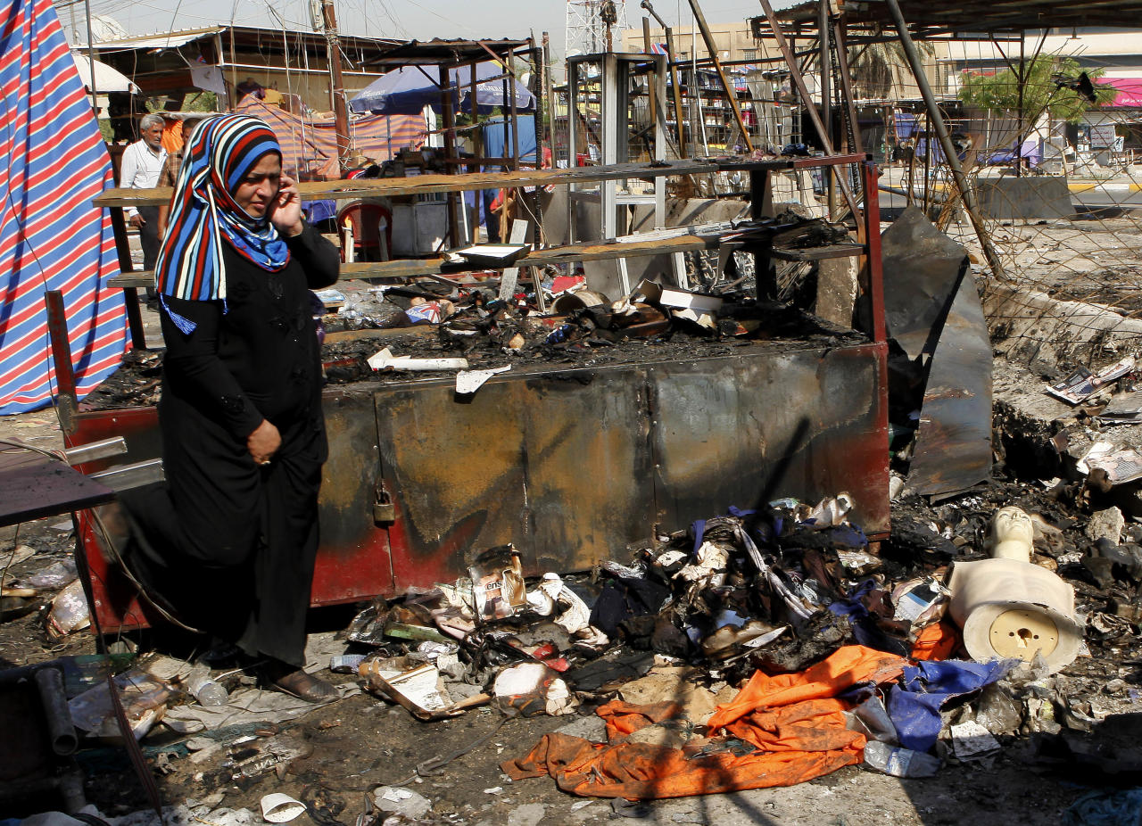 A woman inspect the aftermath of a car bomb attack on a store in the New Baghdad neighborhood of Baghdad, Iraq, Sunday, Aug. 11, 2013. A wave of car bombings targeting those celebrating the end of Ramadan across Iraq killed scores of people Saturday, a bloody reminder of the inability of Iraqi authorities to stop violence threatening to spiral out of control. (AP Photo/Hadi Mizban)