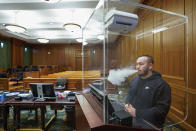 Contractor Jimmy Griffenkranz demonstrates how a HEPA filter works with a smoke test in the attorney's podium surrounded by plexiglass in a courtroom at a Manhattan federal courthouse, Friday, March 12, 2021, in New York. What is arguably the nation's busiest and largest federal courthouse complex took the adage that justice delayed is justice denied to heart when COVID hit. Now, dozens of jury trials in Manhattan are planned with a safety system so extensive that no document will change hands without being sprayed with disinfectant. (AP Photo/Mary Altaffer)
