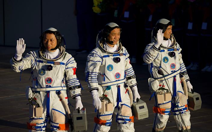 Astronauts (L-R) Tang Hongbo, Nie Haisheng, and Liu Boming depart for the launch site - Visual China Group