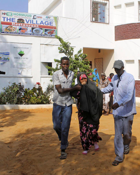 People assist a girl wounded in a suicide blast at popular restaurant in Mogadishu, Saturday, Nov. 3, 2012. A police official says a security guard died while fending off suicide bombers who were trying to storm into a popular Mogadishu restaurant. (AP Photo/Farah Abdi Warsameh)