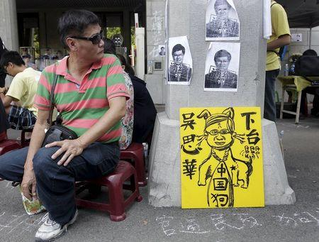 An activist looks at the papers with Taiwan's Education Minister Wu Se-hwa's picture during a protest at the entrance to the Ministry of Education in Taipei, Taiwan, August 1, 2015. REUTERS/Pichi Chuang