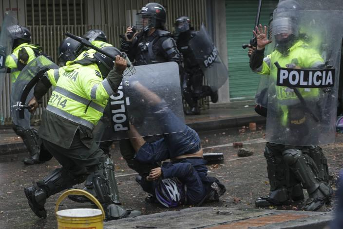 A police officer bears down on an anti-government protester during clashes in Bogota, Colombia, Wednesday, June 9, 2021. The protests have been triggered by proposed tax increases on public services, fuel, wages and pensions. (AP Photo/Ivan Valencia)