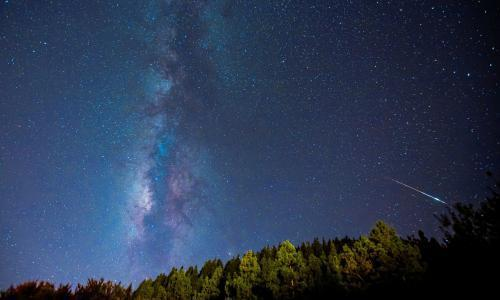 A meteor is photographed near the Milky Way