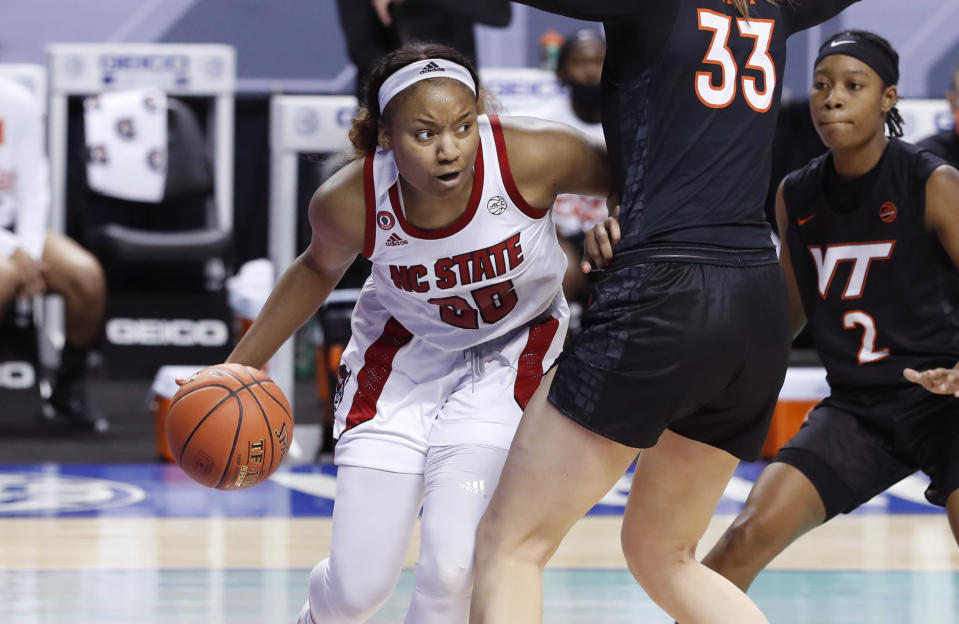 North Carolina State's Kayla Jones (25) drives around Virginia Tech's Elizabeth Kitley (33) during the first half of an NCAA college basketball game in the Atlantic Coast Conference women's tournament in Greensboro, N.C., Friday, March 5, 2021. (Ethan Hyman/The News & Observer via AP)